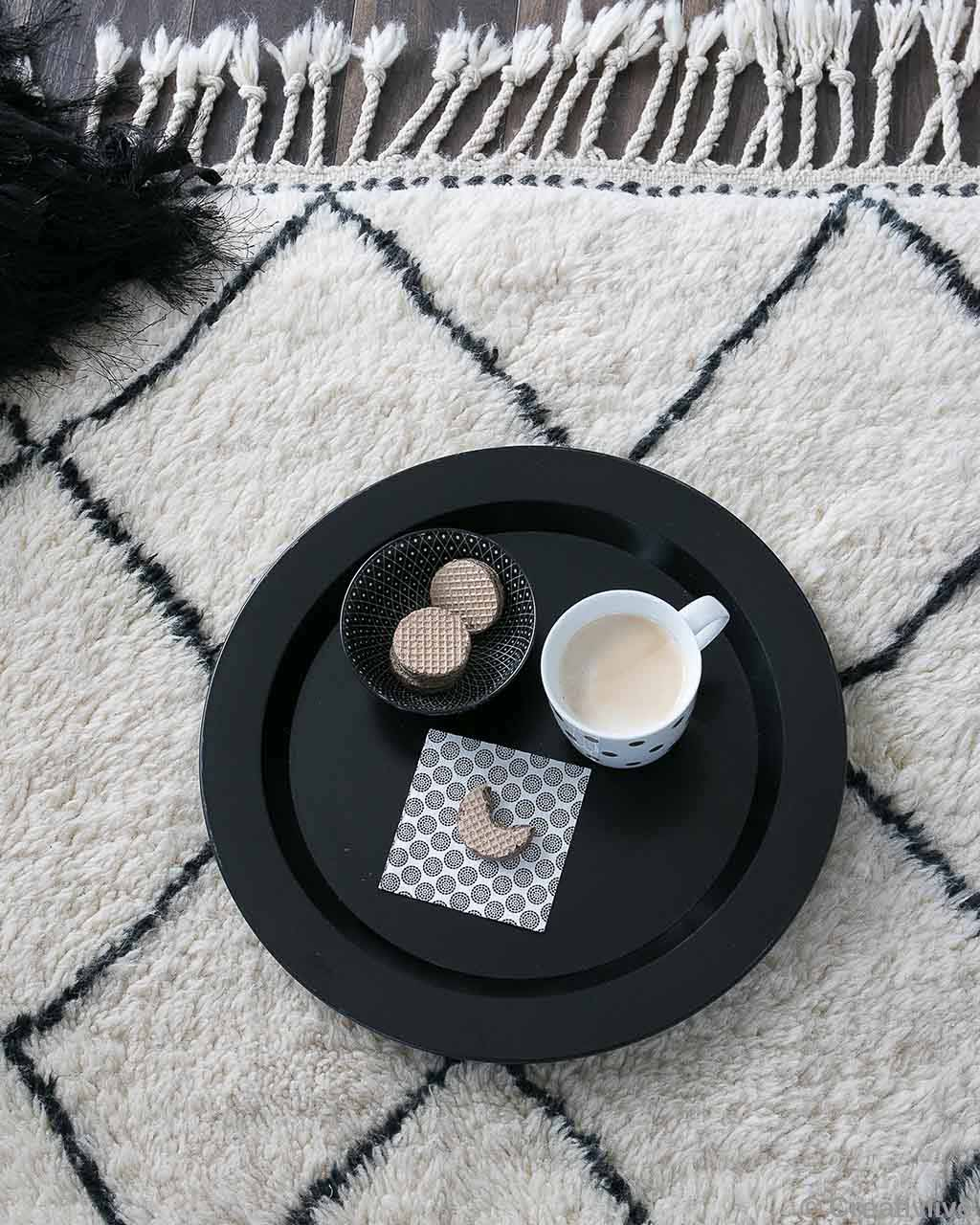 biscuits in bowl and tea cup in tray asian traditional carpet